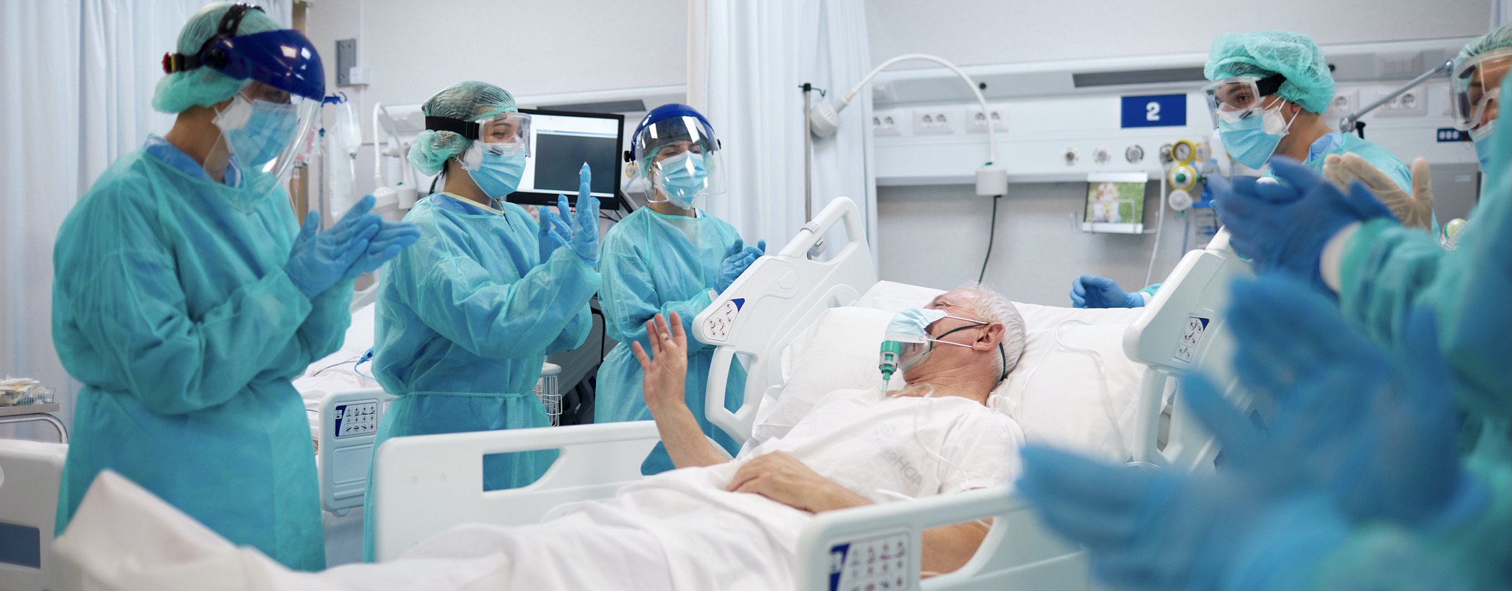 Healthcare professionals clapping for a recovered COVID patient